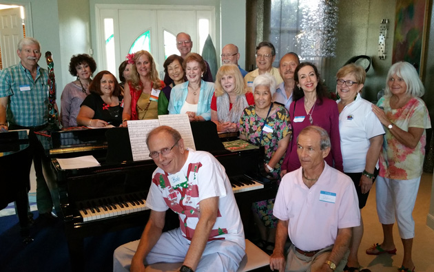 A lively group attended the 2014 Southeast Florida holiday party in December. Bob Petrik , our Host, in foreground played on his piano sing a long Holiday Carols For group that attended TCC S.E. Fla. Holiday Party. Second from right is Cecelia Rokuset, the hostess.  Everybody also brought a wrapped travel souvenir for Gift exchange!