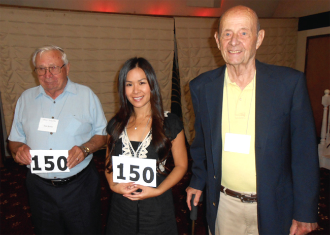 Tim Carlson congratulates Nick Bowles and Lucy Hsu on reaching 150 countries and territories.