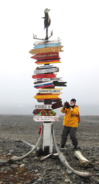 Frank Rainer is pictured with directional signs at the Uruguayan Artigas Station on King George Island.
